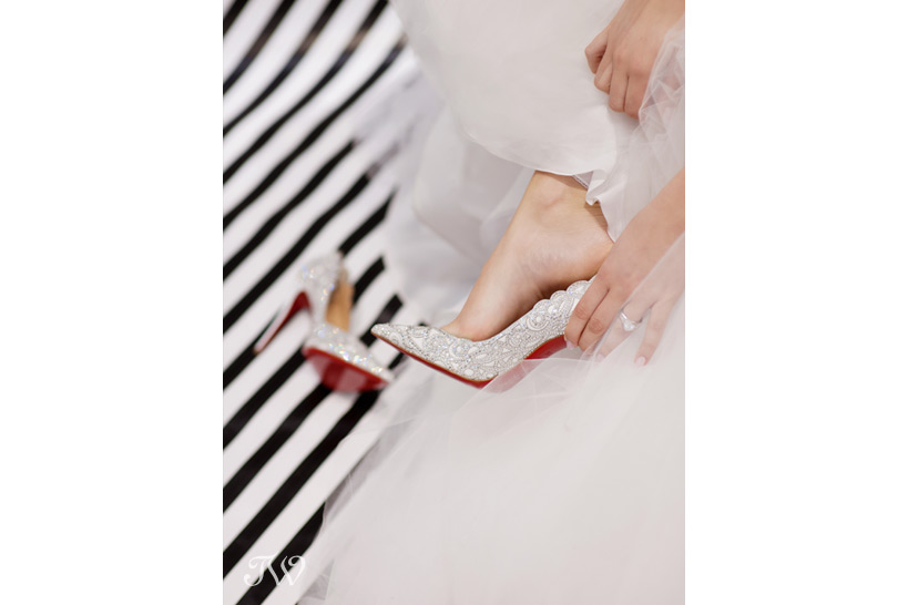 bride putting on Christian Louboutin bridal shoes Tara Whittaker Photography
