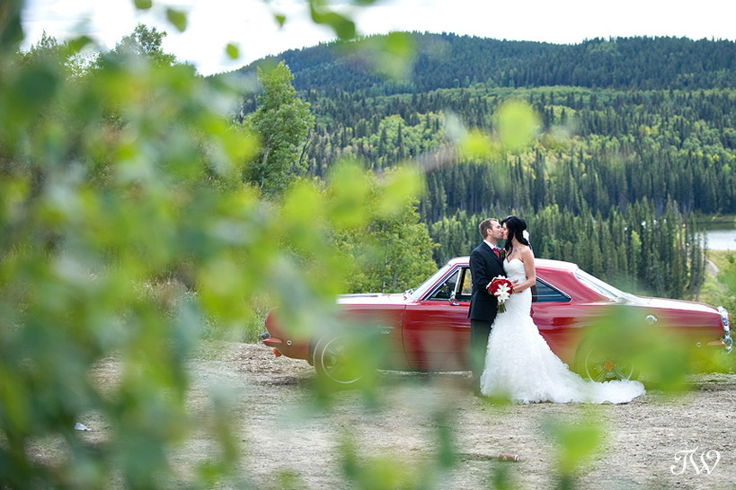 bride and groom with a red car photographed by Tara Whittaker