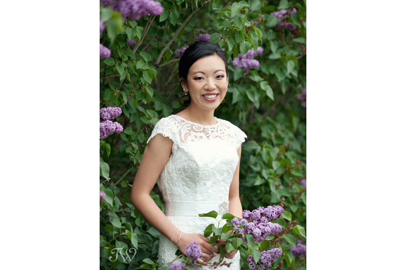a bride poses with purple lilacs captured by Tara Whittaker Photography