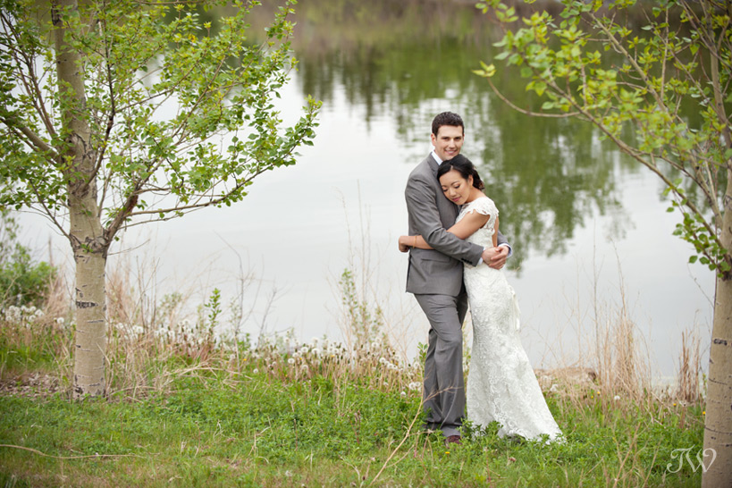 bride and groom pose by a lake Tara Whittaker Photography