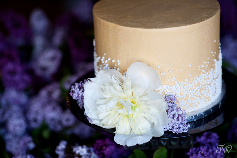 wedding cake surrounded by lilac blooms captured by Tara Whittaker Photography