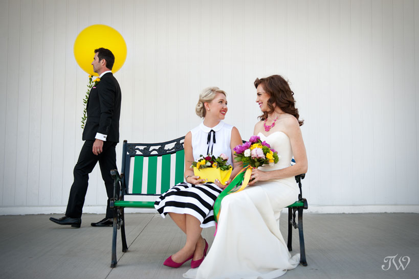 bride and her bridesmaid on a bench captured by Tara Whittaker Photography
