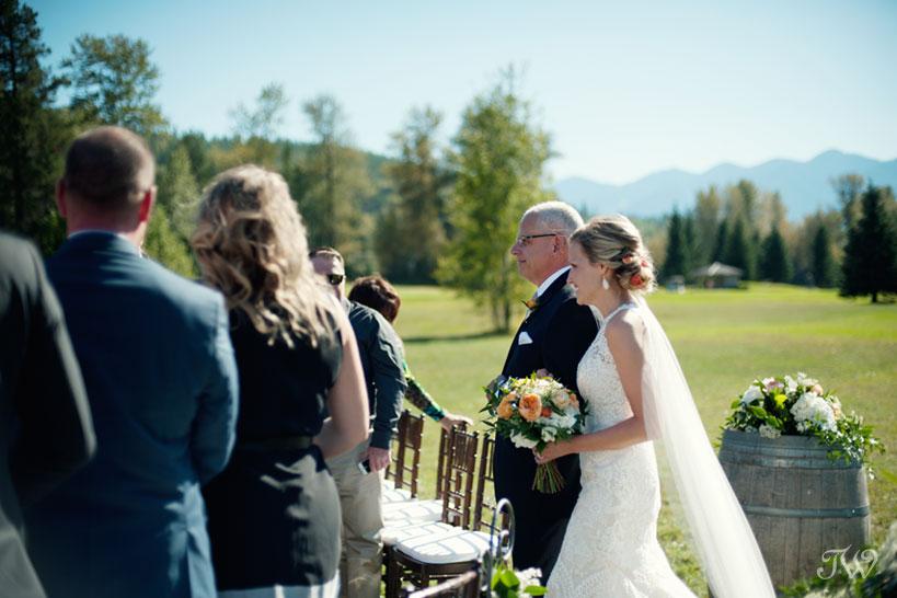 Bride walks down the aisle at her Fernie wedding captured by Tara Whittaker Photography