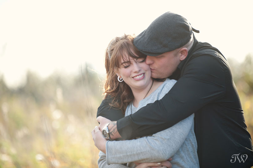 couple embrace during their engagement session in Calgary captured by Tara Whittaker Photography