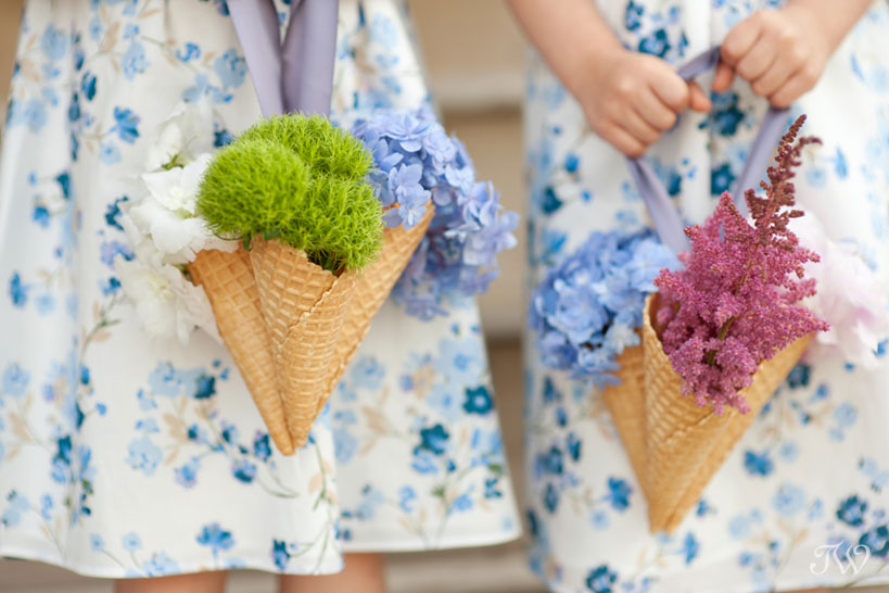 two flower girls holding ice cream cones filled with flowers