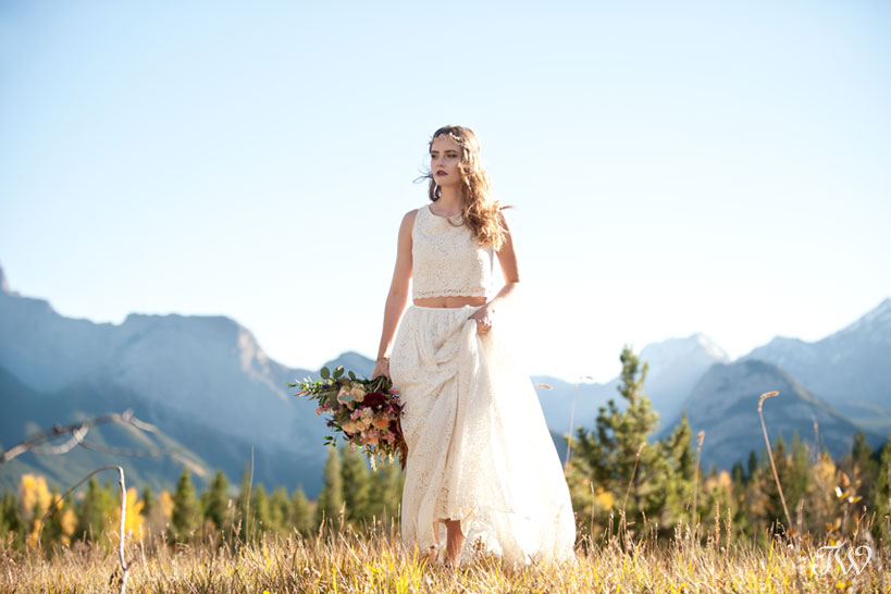 bohemian bride walks with Rocky Mountains behind her captured by Calgary wedding photographer Tara Whittaker