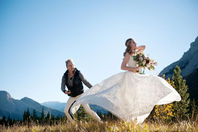 stylist Erica Piebiak arranges the bride's gown captured by Calgary wedding photographer Tara Whittaker