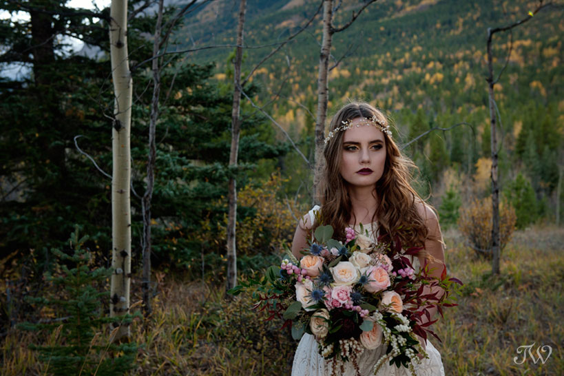 bohemian bride with her bouquet accented by berries grasses and leaves