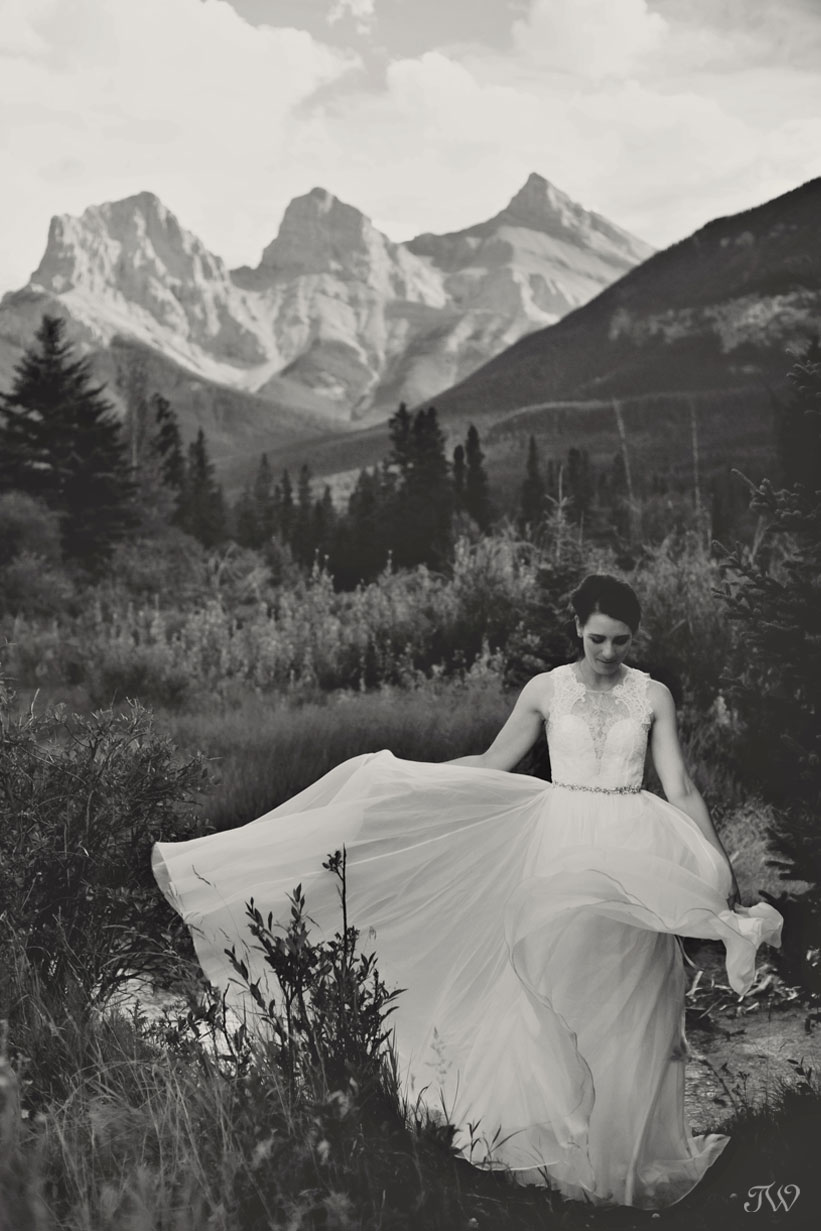 bride's gown blows in the breeze near The Three Sister in Canmore