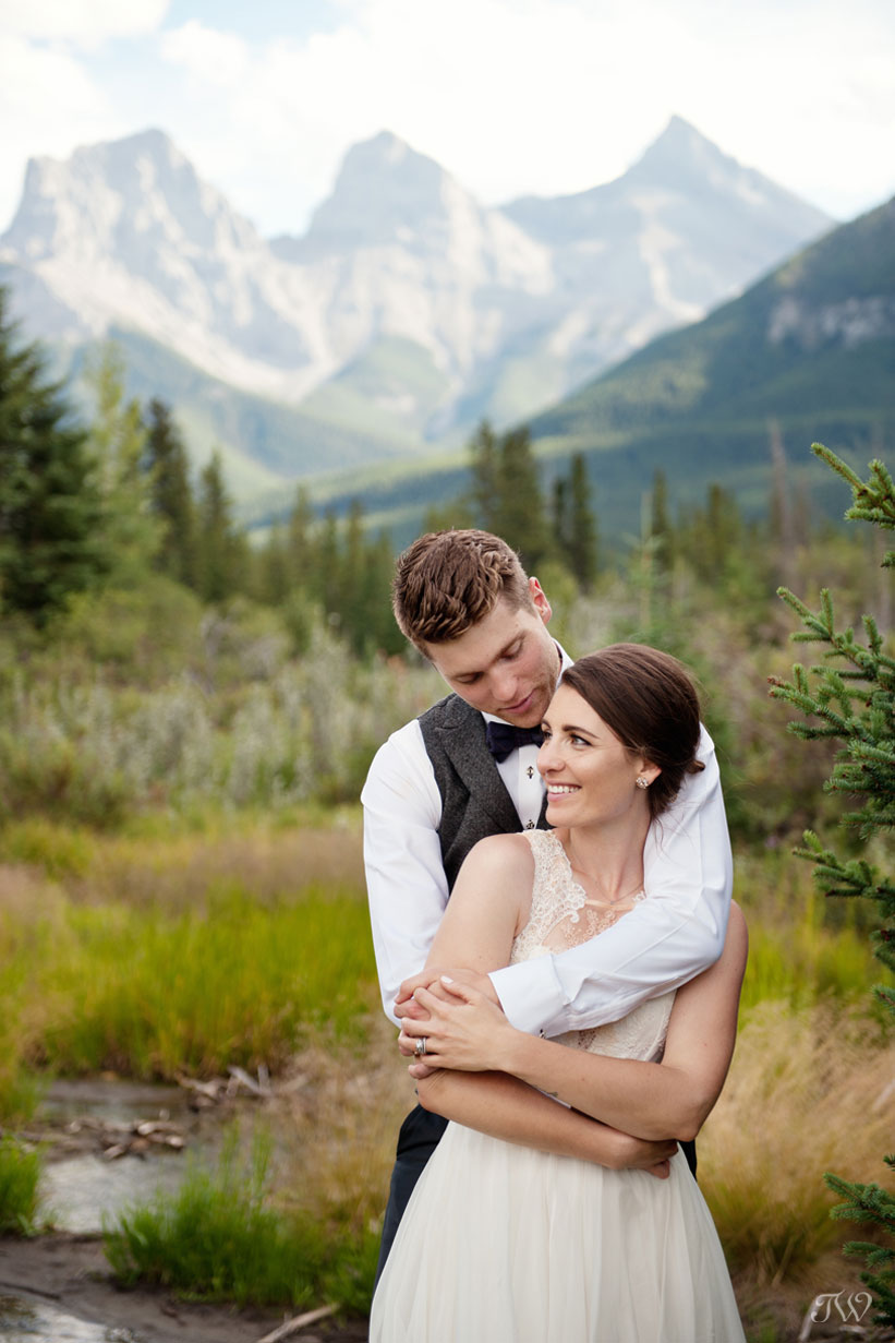 couple pose in front of The Three Sisters in Canmore Tara Whittaker Photography