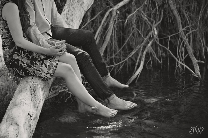 couple dip their toes in the river during engagement pictures by Tara Whittaker Photography