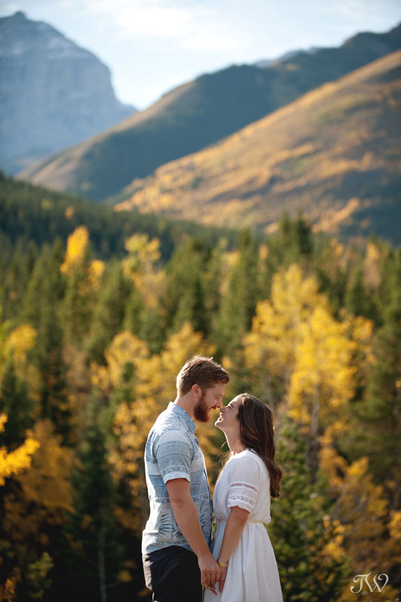 yellow trees and mountain peeks as a backdrop for a fall engagement session