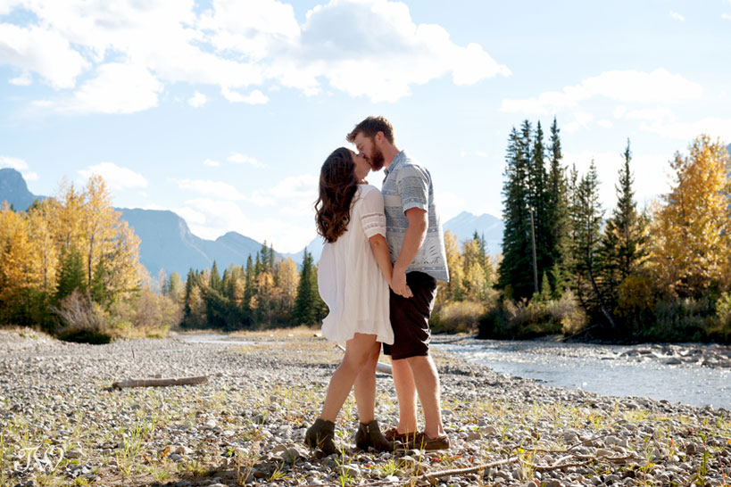 couple kiss beside the Kananaskis River during their fall engagement session