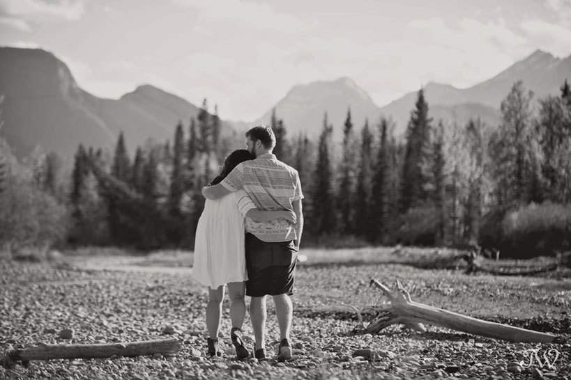 couples stroll along the Kananaskis River during their fall engagement session