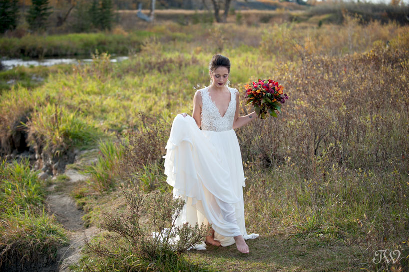 fall bride walks through Fish Creek Park captured by Calgary wedding photographer Tara Whittaker