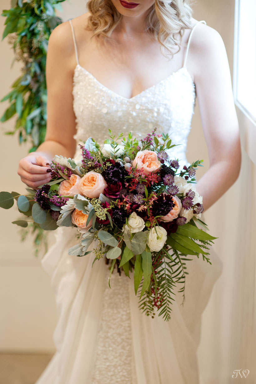 winter bride carries a bouquet in berry tones captured by Calgary wedding photographer Tara Whittaker