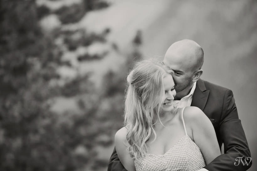 Caitie and Mark embrace at their Spray Lakes engagement session captured by Tara Whittaker Photography