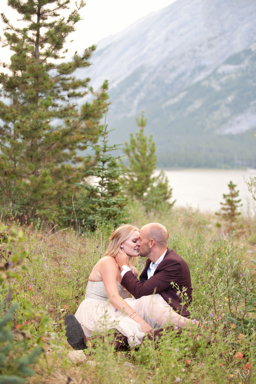 Caitie and Mark sit in the wildflowers at their Spray Lakes engagement session captured by Tara Whittaker Photography