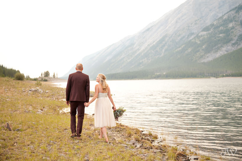 Couple on the shore of Spray Lakes captured by Calgary wedding photographer Tara Whittaker