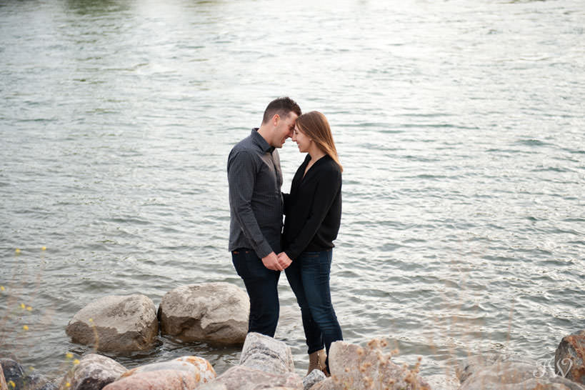 Couple on banks of Bow River during East Village engagement session captured by Tara Whittaker Photography
