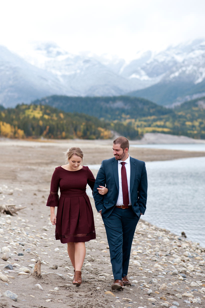bride and groom stroll on the shore of Barrier Lake captured by Calgary wedding photographer Tara Whittaker