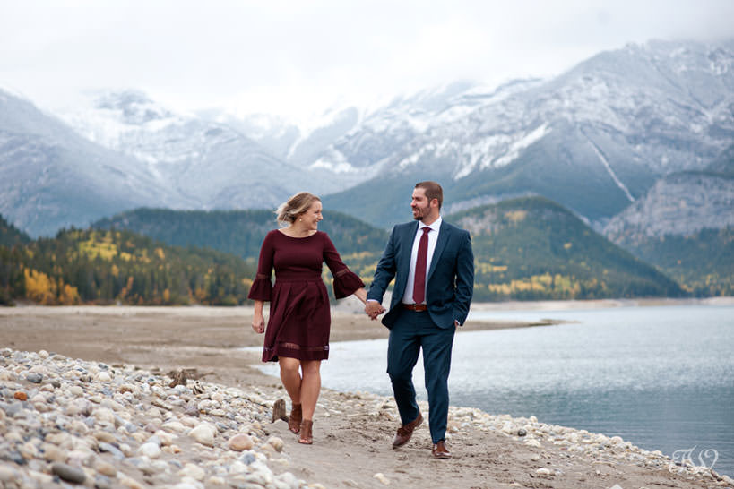 bride and groom stroll on the shore of Barrier Lake in Kananaskis captured by Tara Whittaker Photography