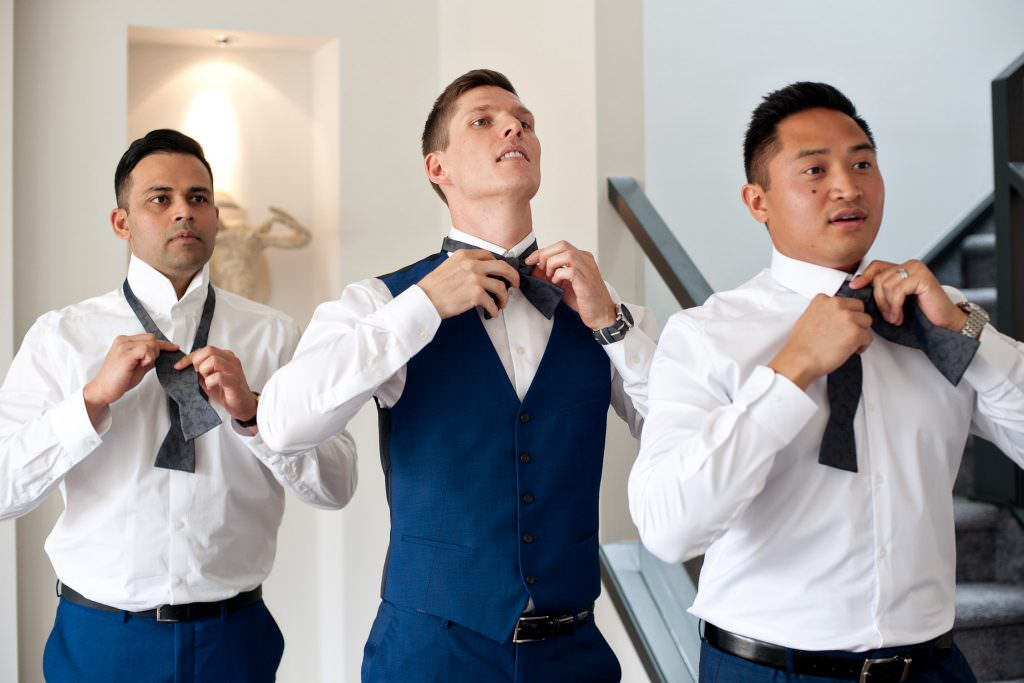 groom tying his bow tie before his classic wedding at Alloy Restaurant