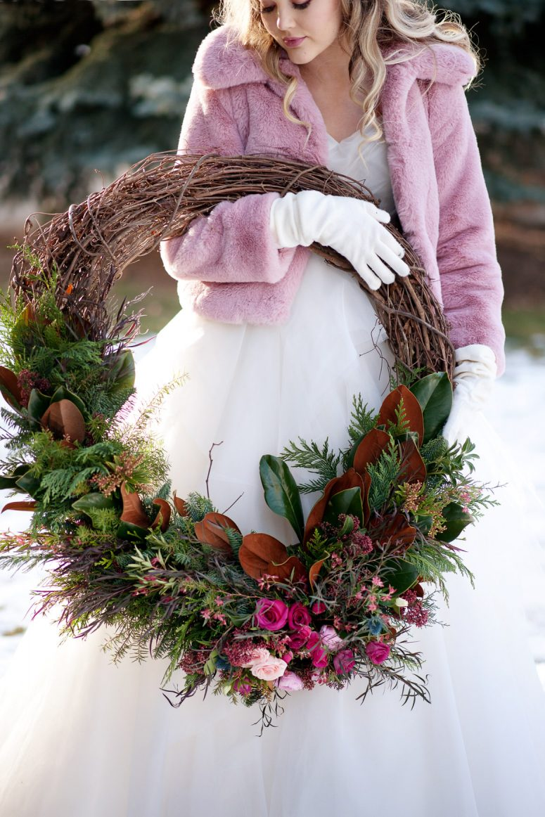 winter bride holding a wreath captured by one of the best wedding photographers in Calgary Tara Whittaker