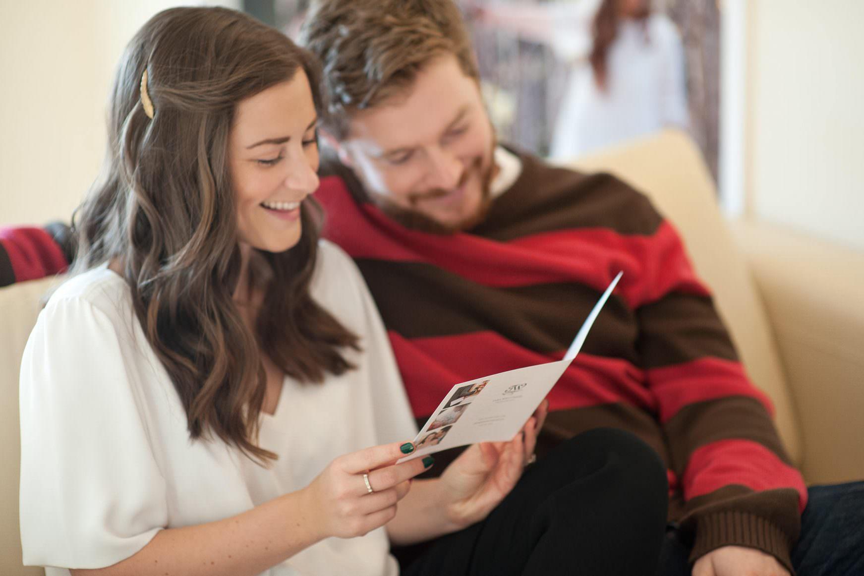 couple viewing price list for Calgary wedding photographer Tara Whittaker
