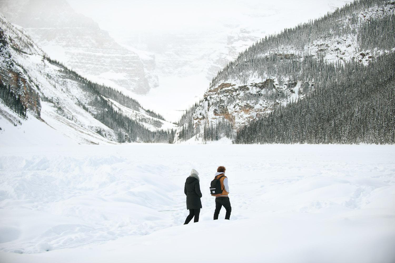 couple walk on frozen ice at Lake Louise captured by Calgary wedding photographer Tara Whittaker