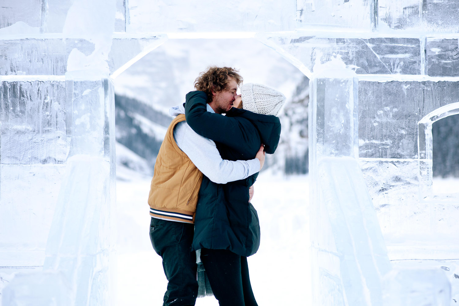 couple pose with ice castle at Lake Louise during engagement session captured by Tara Whittaker Photography
