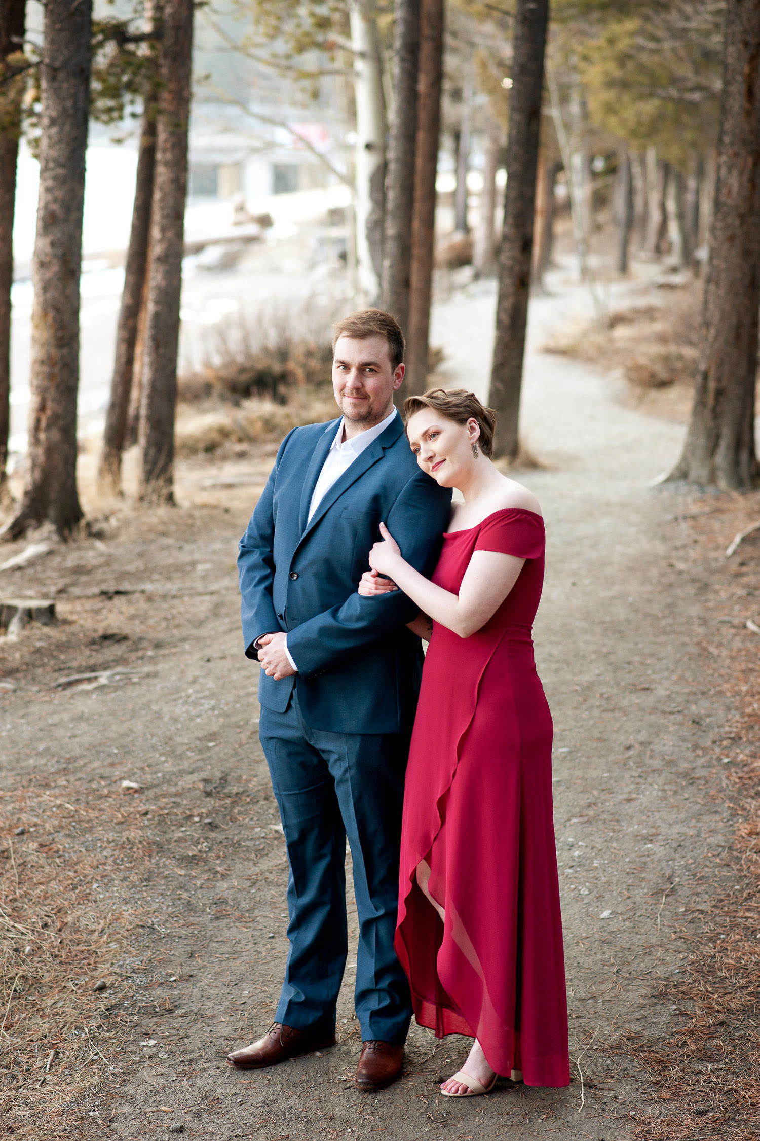 Engaged couple on the shore of Lake Minnewanka Calgary wedding photographer Tara Whittaker