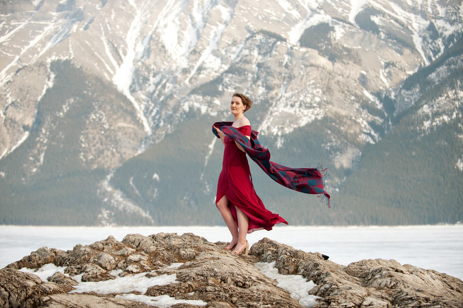 Roseanne in a red dress and tartan scarf at Lake Minnewanka Calgary wedding photographer Tara Whittaker