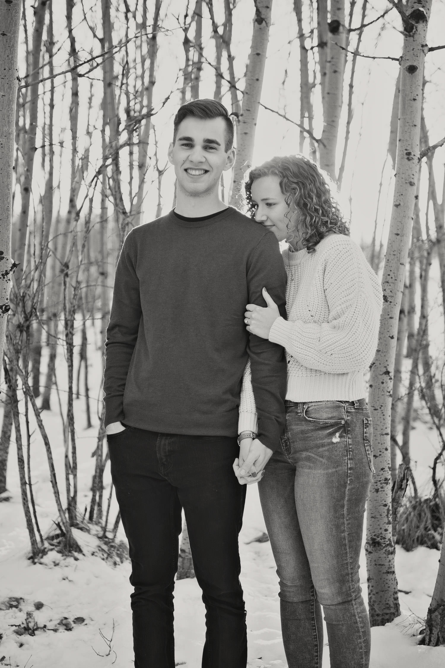 couple in the trees during their winter engagement session captured by Tara Whittaker Photography
