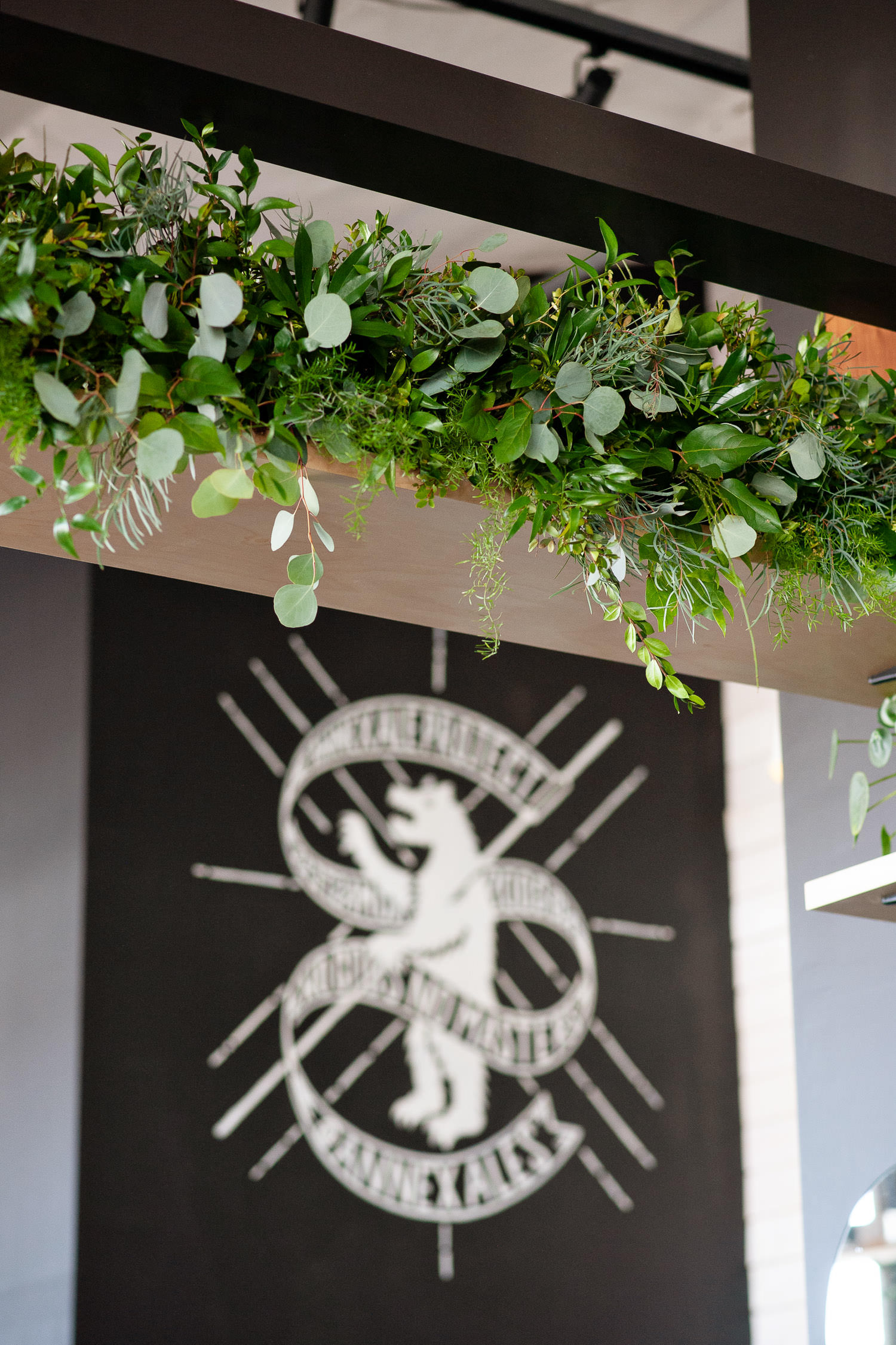 Greenery from Sweet Bloom adorns the ceremony space at Annex Ale Project
