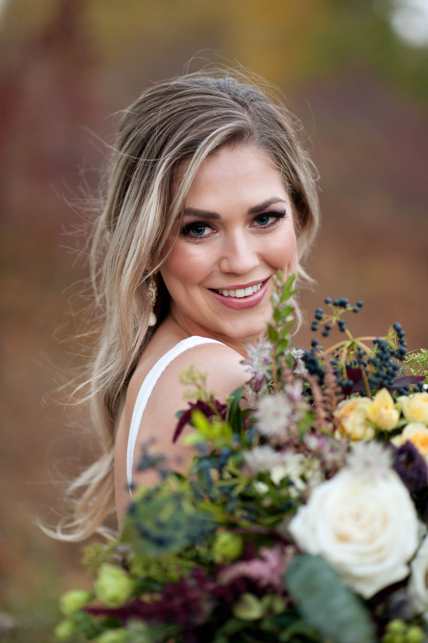 bride carries fall bridal bouquet from Fleurish Flower Shop captured by Tara Whittaker Photography