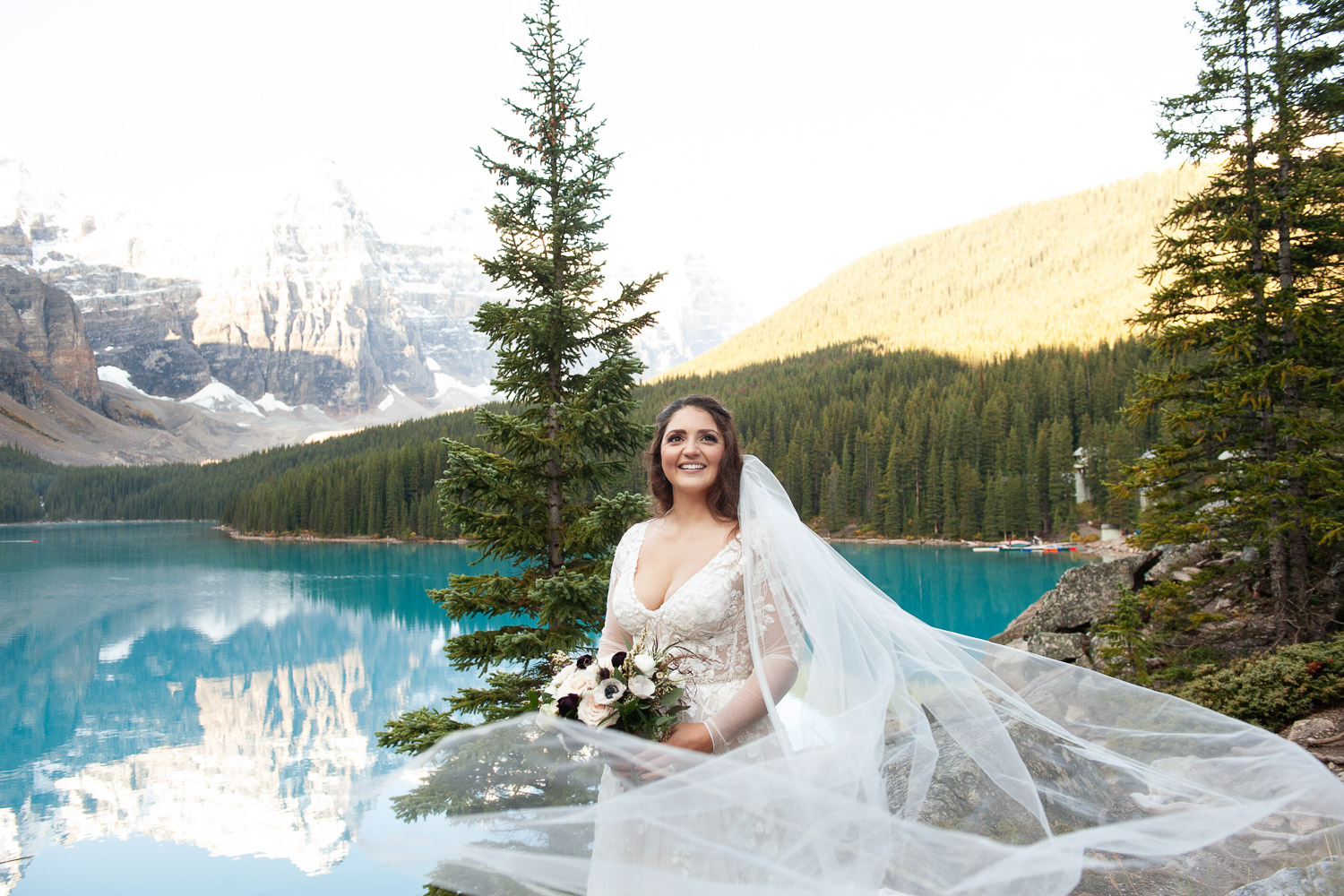 bride's veil blowing in the wind at Moraine Lake captured by Tara Whittaker Photography