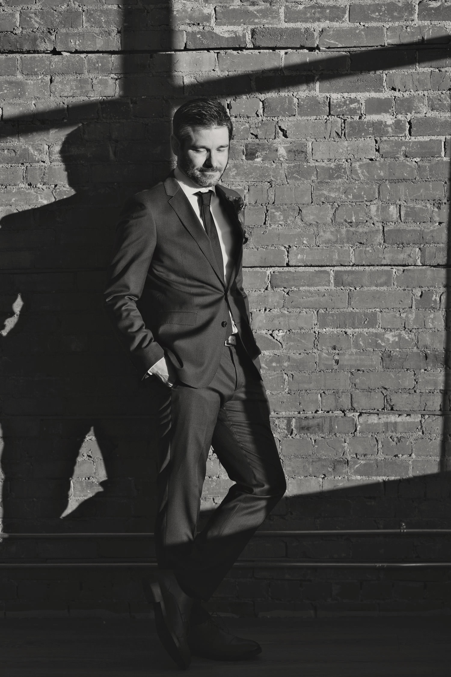 groom poses in front of exposed brick wall at Venue 308 captured by Tara Whittaker Photography