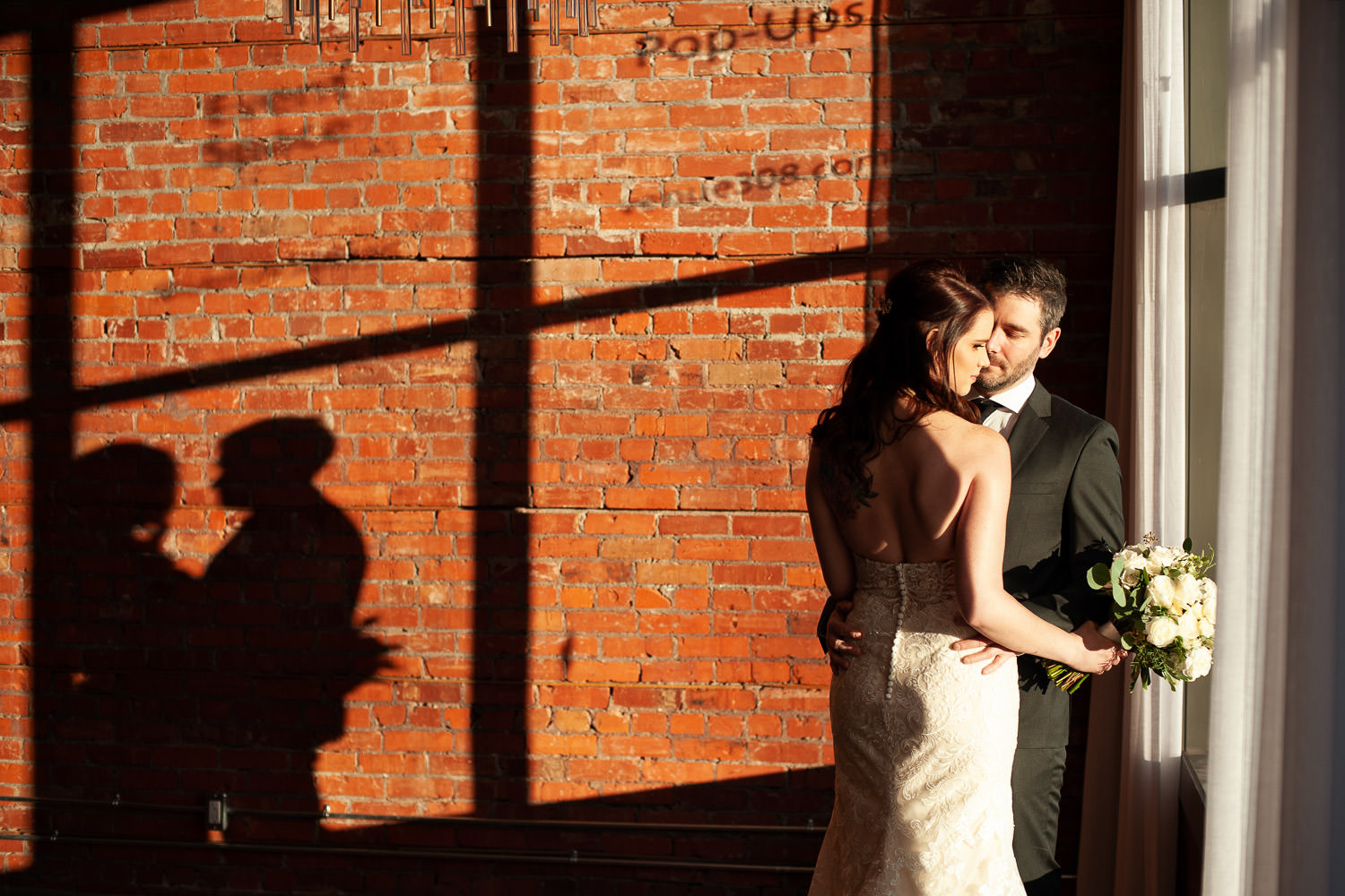 shadow of bride and groom cast on wall at Venue 308 captured by Tara Whittaker Photography