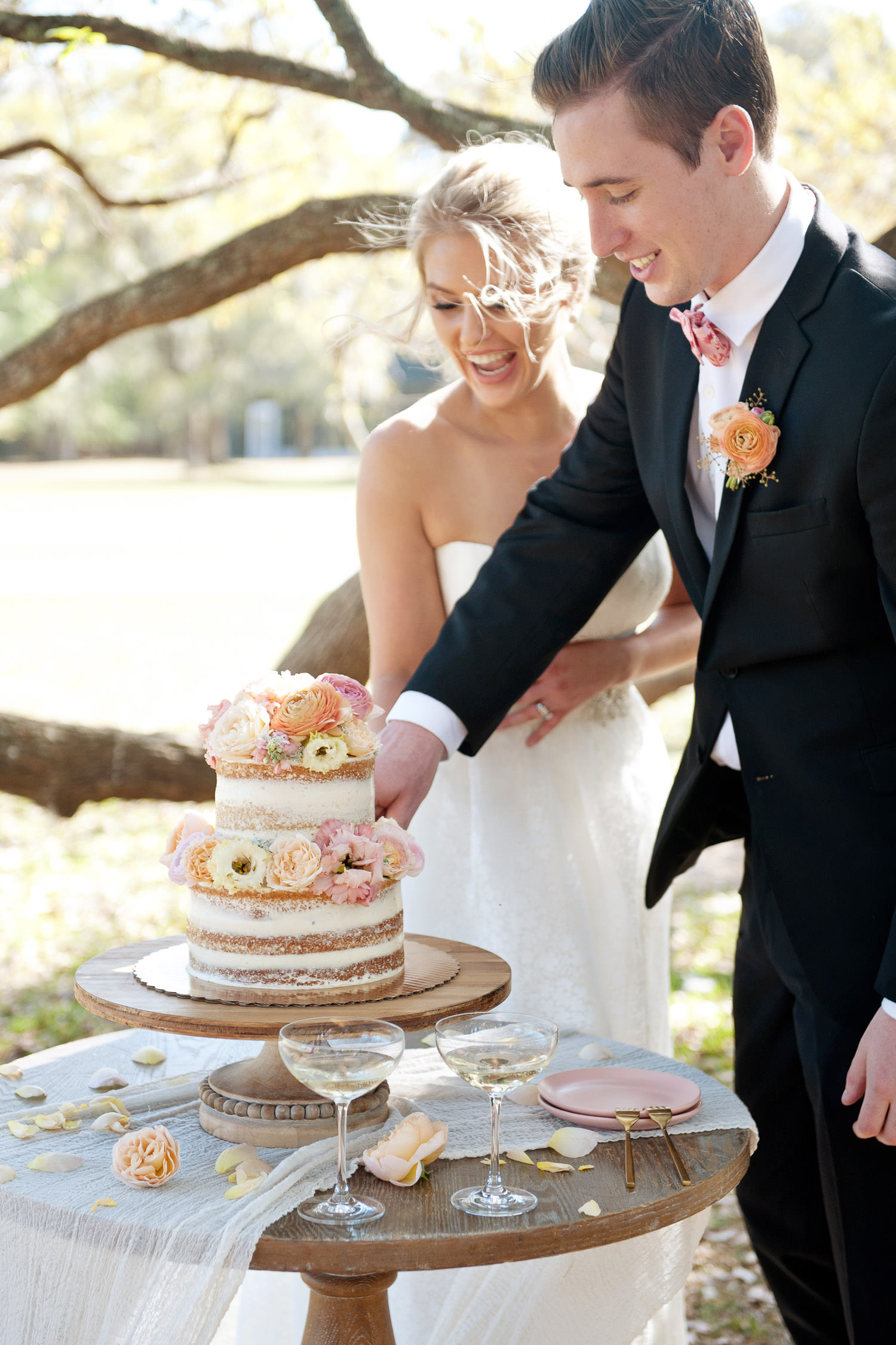bride and groom cut the cake at their garden wedding captured by Tara Whittaker Photography
