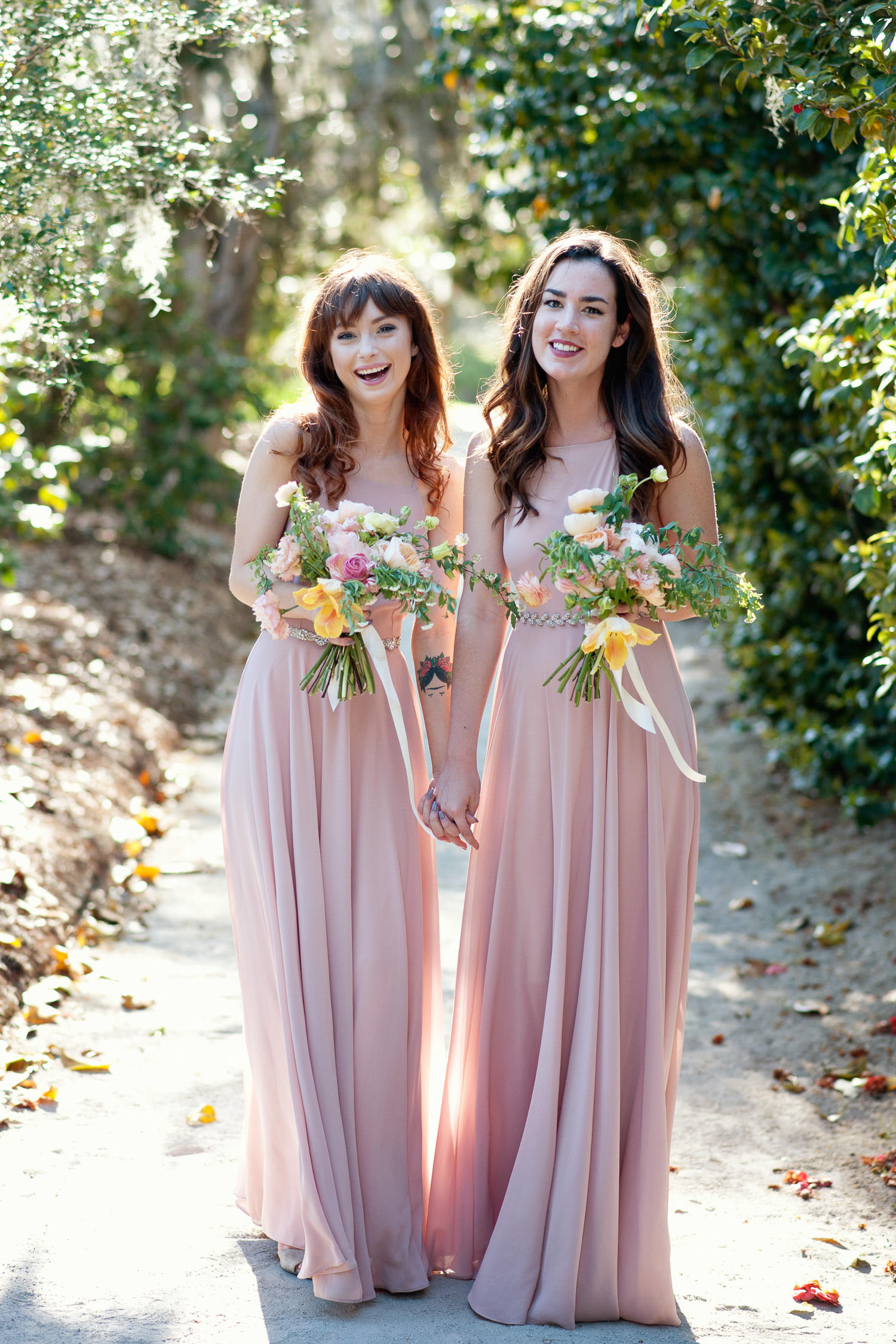 two bridesmaids wearing rose-colored gowns captured by Tara Whittaker Photography
