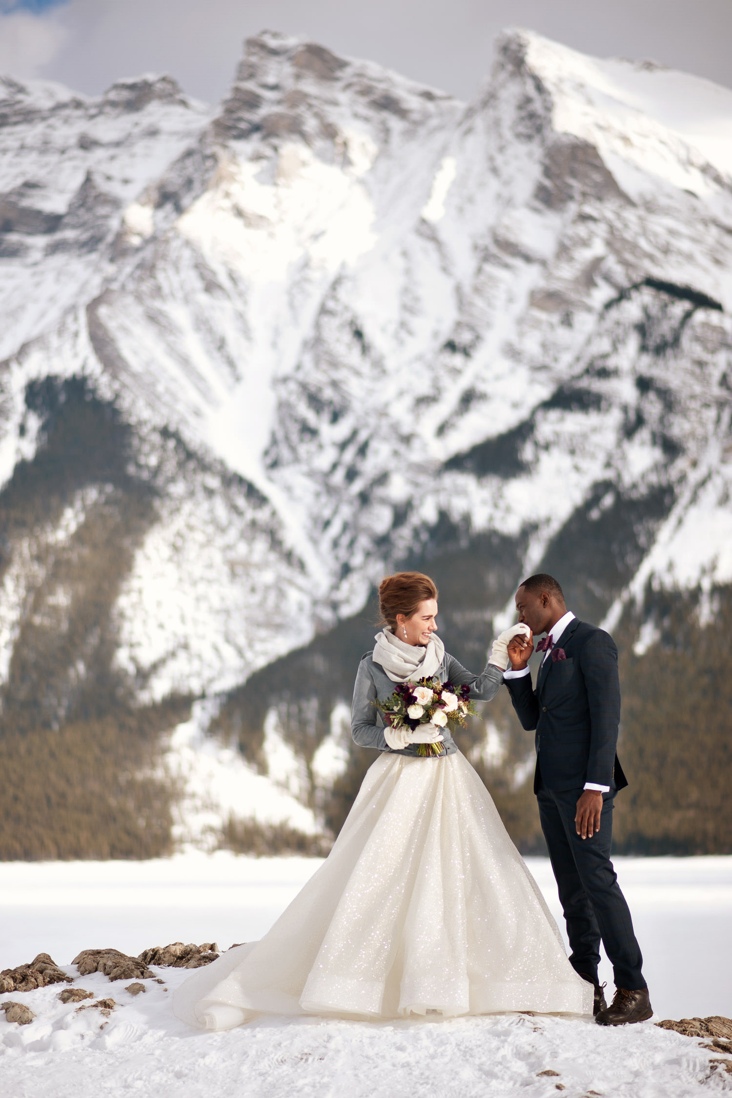 groom kisses his bride's hand at Lake Minnewanka captured by Tara Whittaker Photography