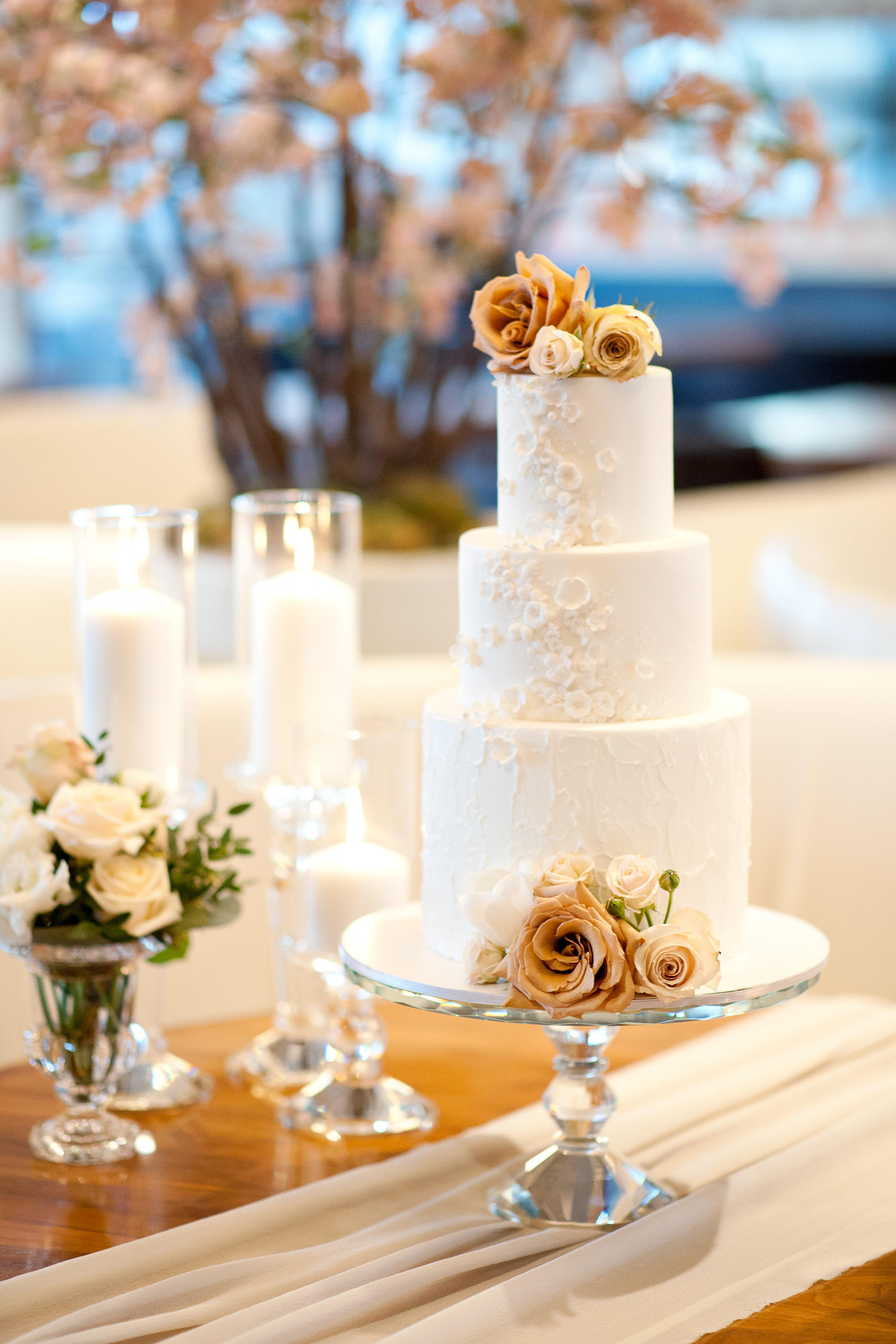 white wedding cake adorned with roses captured by Tara Whittaker Photography