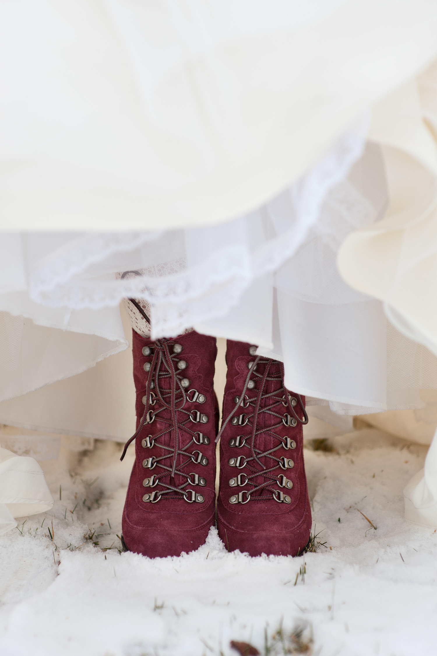 winter bride wears wine-colored boots with her wedding gown captured by Tara Whittaker Photography