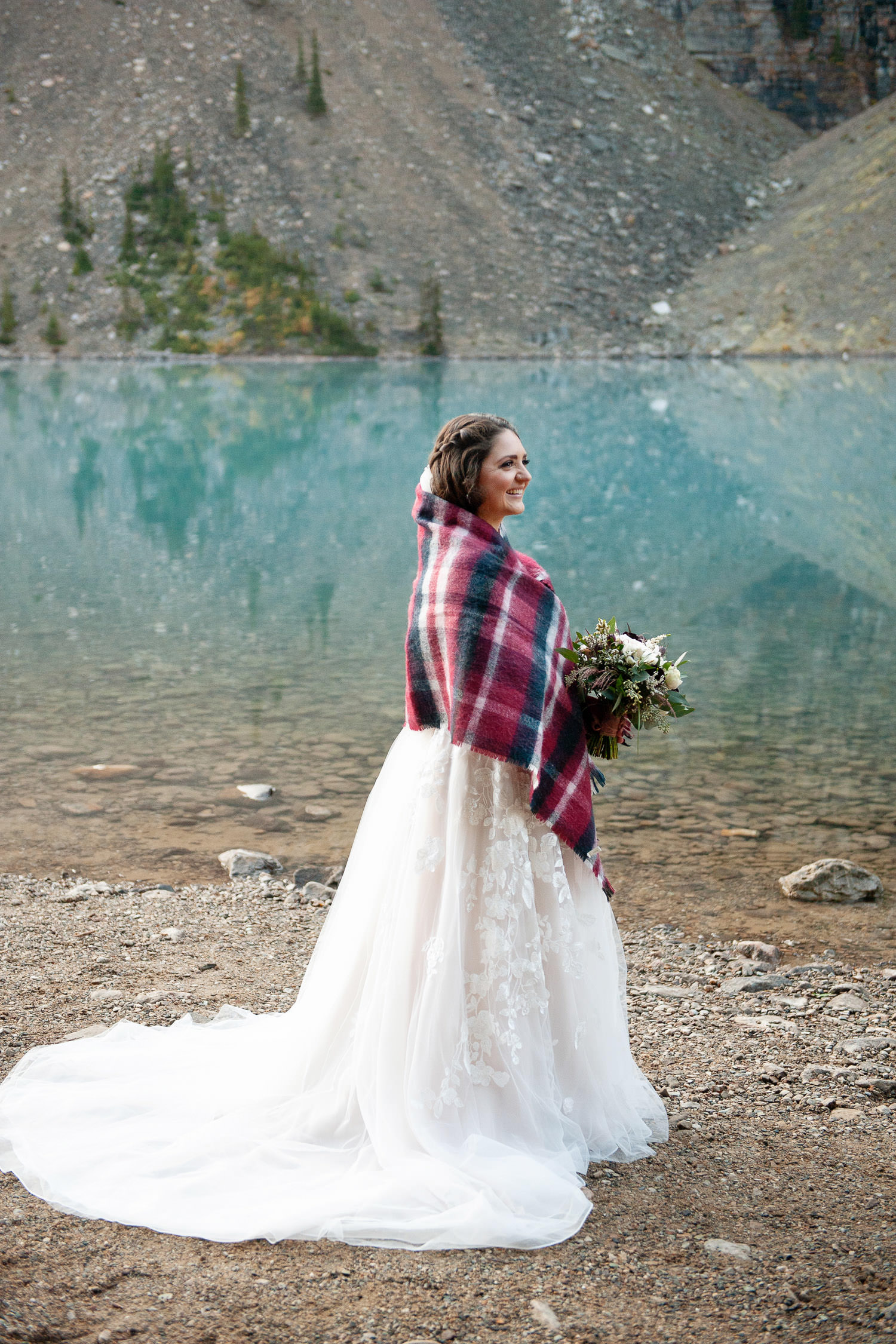 Moraine Lake bride wrapped in a plaid blanket captured by Tara Whittaker Photography