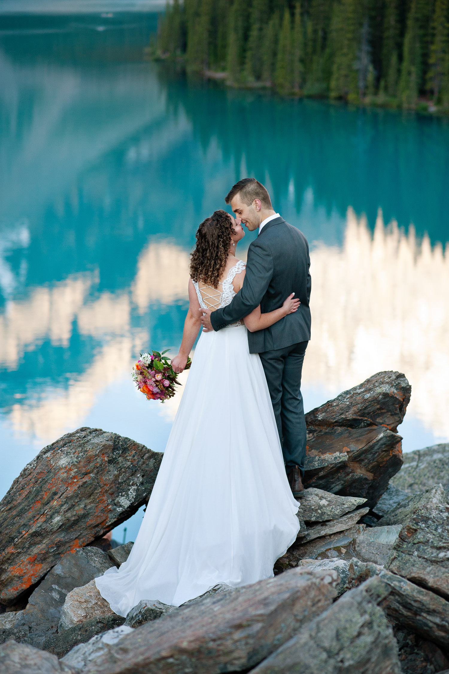 bride and groom on the Rockpile above Moraine Lake captured by Tara Whittaker Photography