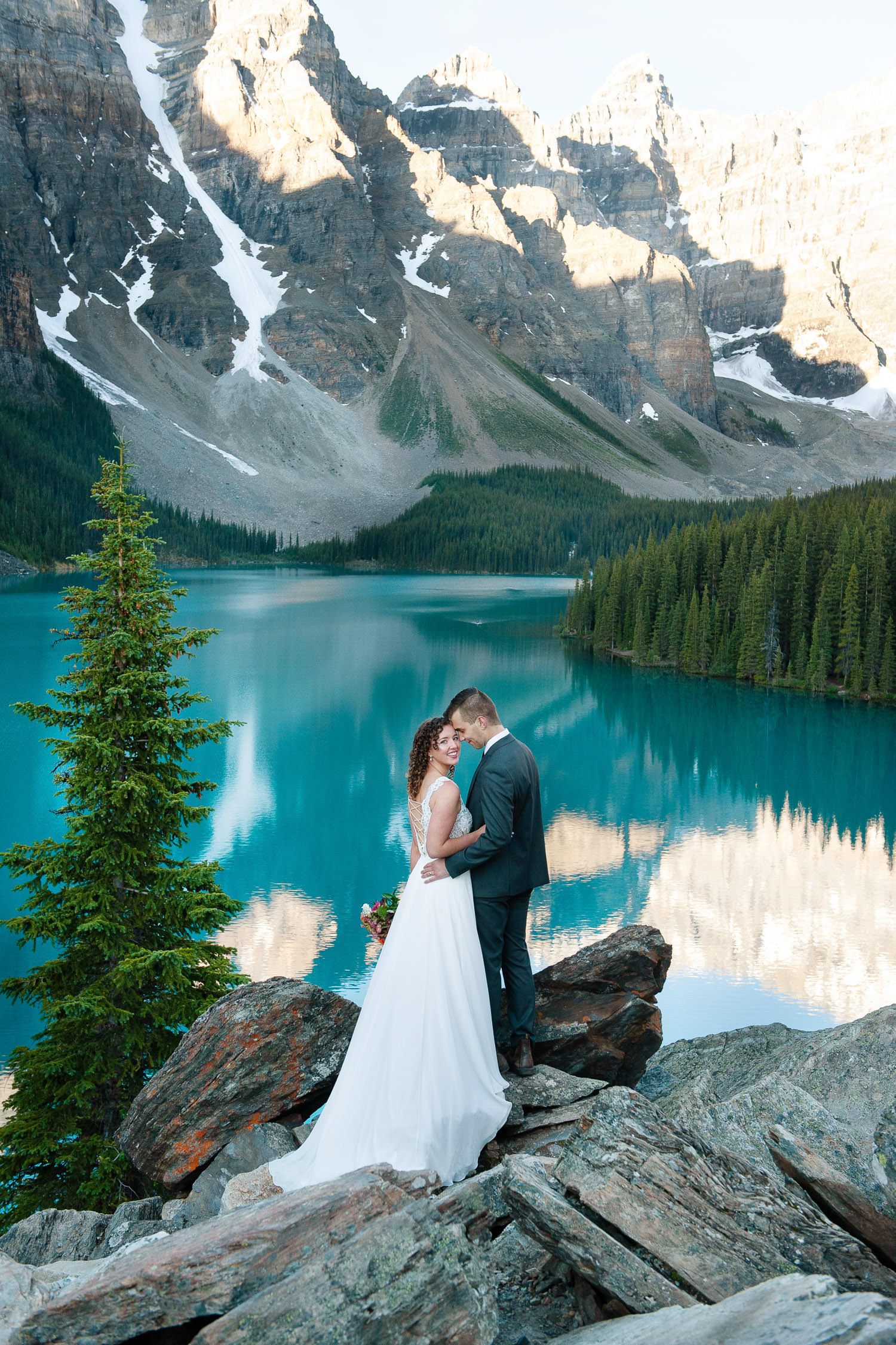 bride and groom at sunrise overlooking Moraine Lake captured by Tara Whittaker Photography