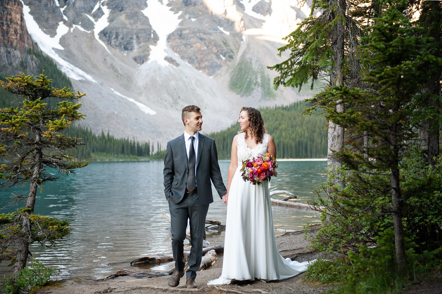 bride and groom walk along the shore of Moraine Lake captured by Tara Whittaker Photography