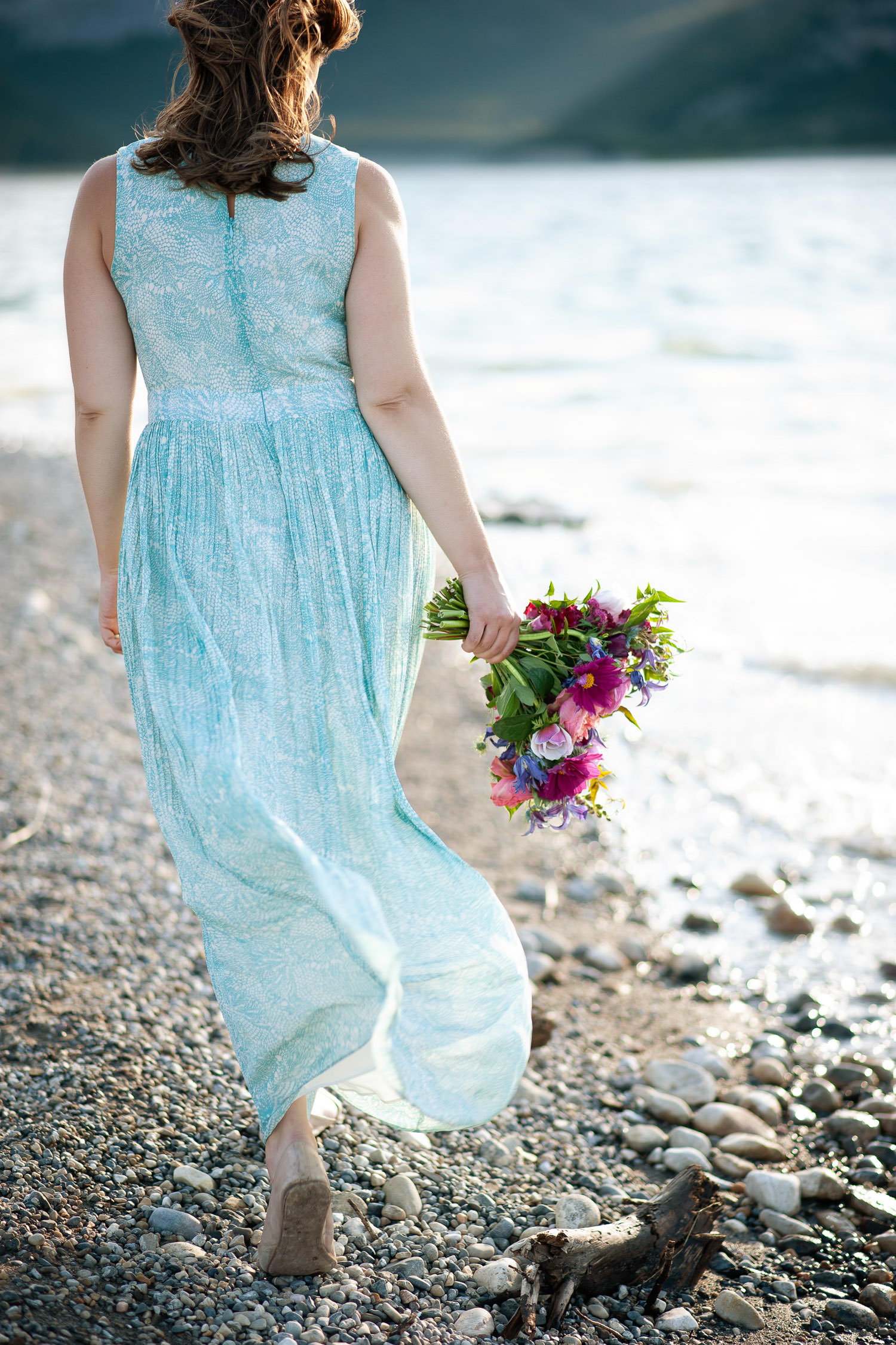 Bride carries a summer bouquet at Barrier Lake captured by Tara Whittaker Photography