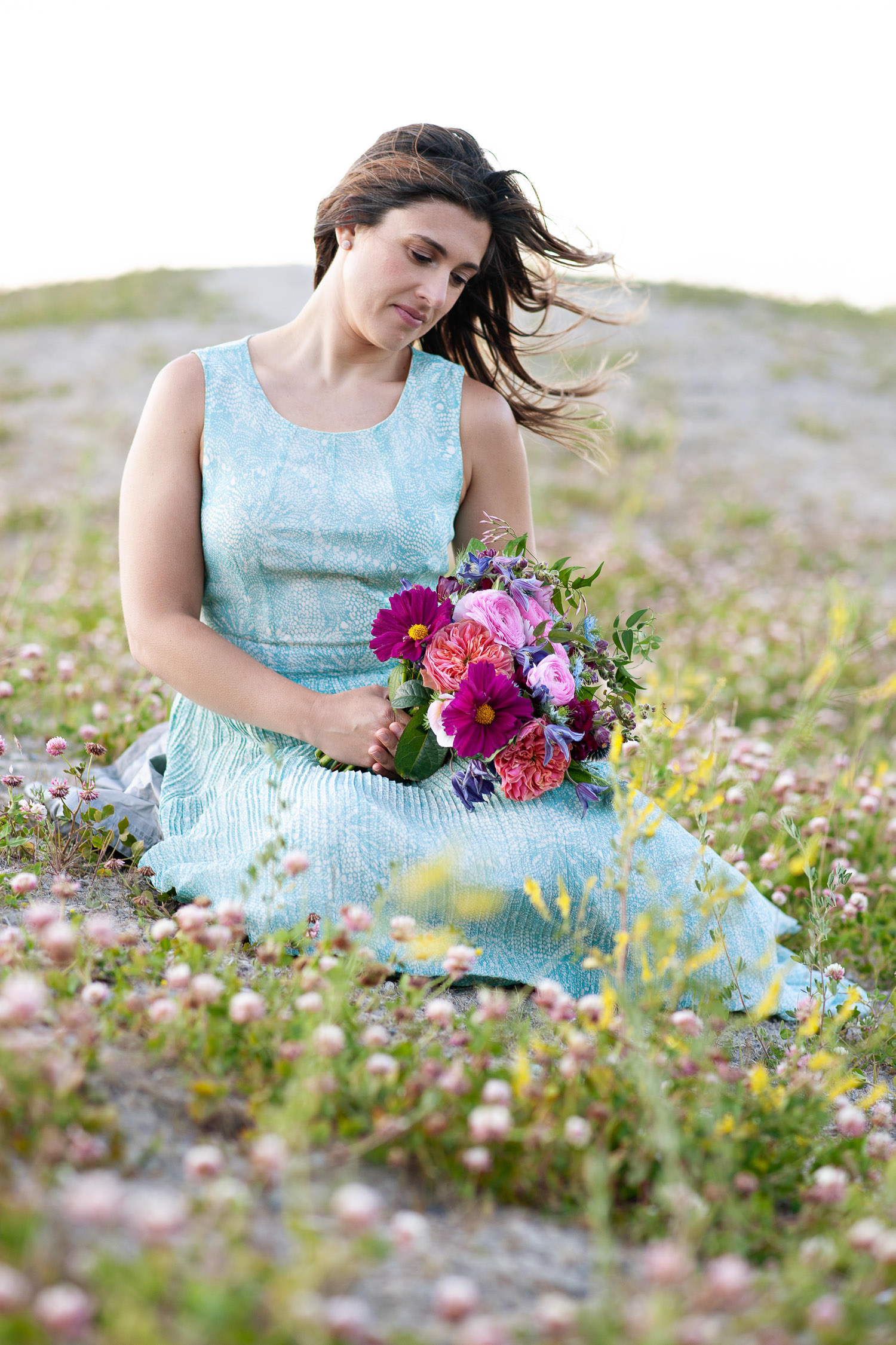 Bride sits among wildflowers at Barrier Lake captured by Tara Whittaker Photography